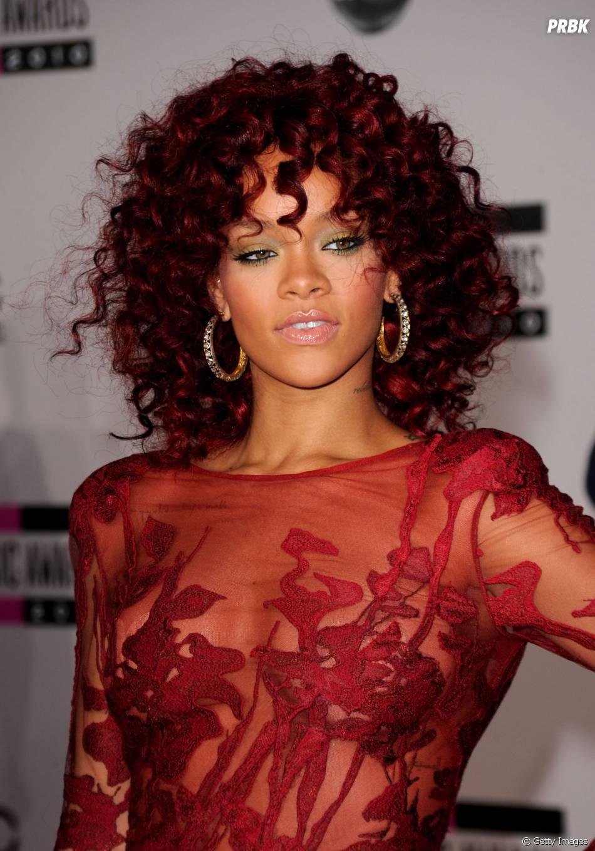 Em um elegante vestido vermelho, as rendas do look tamparam mamilo de Rihanna