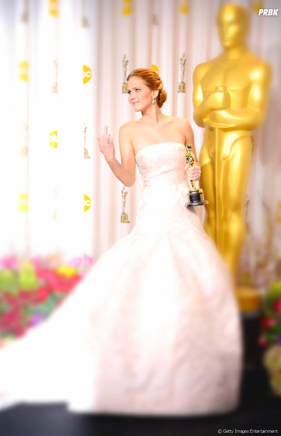 Durante o Oscar 2013, Jennifer Lawrence levanta dedo para os fotógrafos