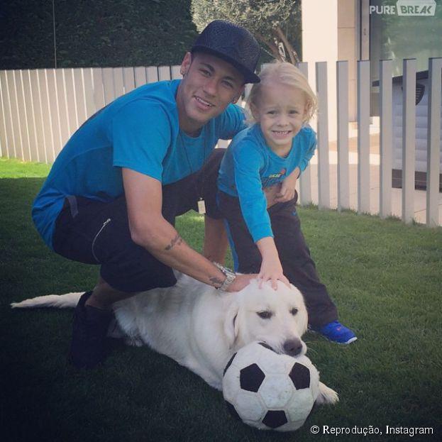 Neymar Jr. e o filho, Davi Lucca, brincam com o cachorro Poker