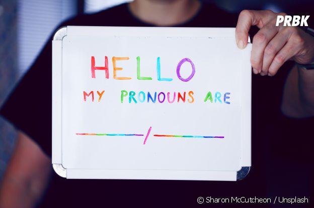 """Placa diz: """"Olá, meus pronomes são..."""""""