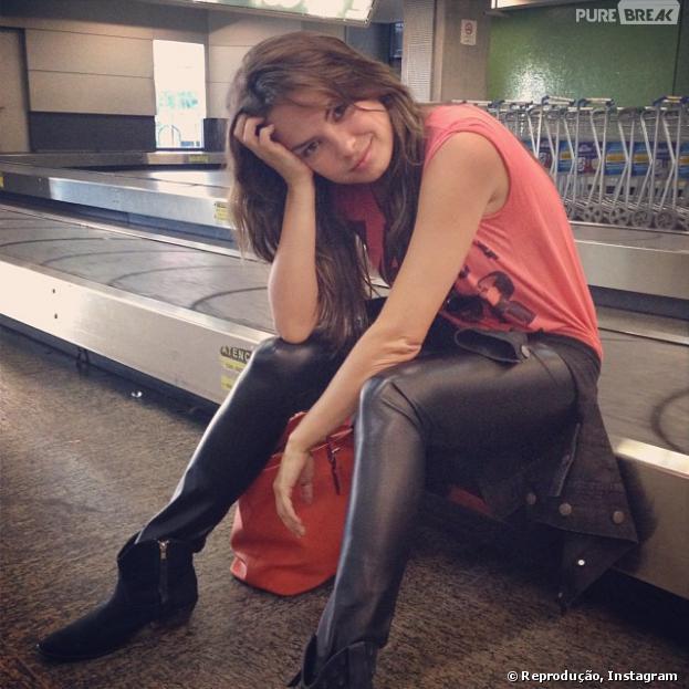 A atriz Lua Blanco se diverte sentada na esteira do aeroporto