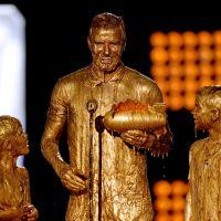 David Beckham e os filhos tomam banho de tinta dourada em premiação infantil