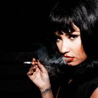 Demi Lovato fuma, faz carão e deixa pernas à mostra em ensaio sensual