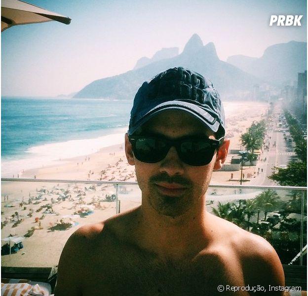 Joe Jonas posa em hotel na zona sul do Rio com praia de Ipanema ao fundo