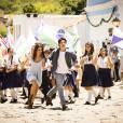 """Helena (Julia Dalavia) e Laerte (Eike Duarte) correm no meio de uma parada na novela """"Em Família"""""""