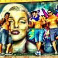 Caio Castro sem camisa posa na frente de um grafite da Marilyn Monroe