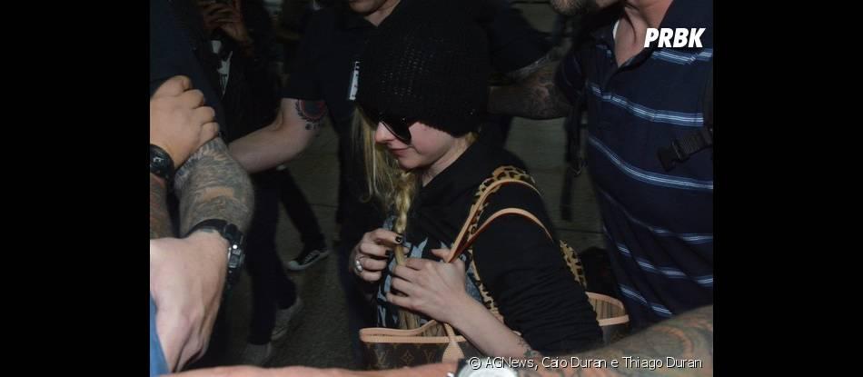 De gorro e óculos escuros, Avril Lavigne desembarcou no aeroporto de Guarulhos, em São Paulo