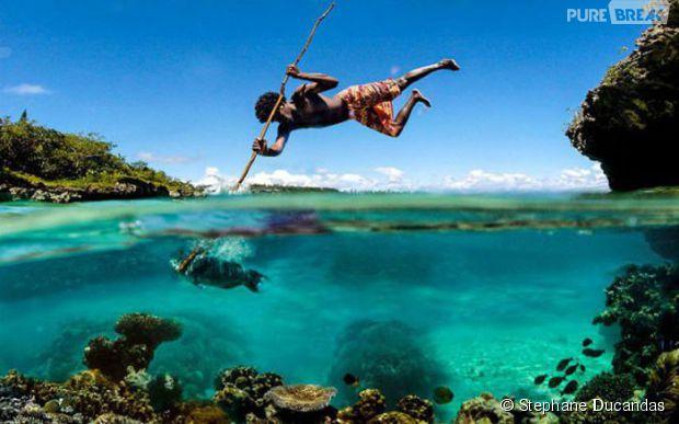 Pescador no momento exato em que arpoou o peixe!