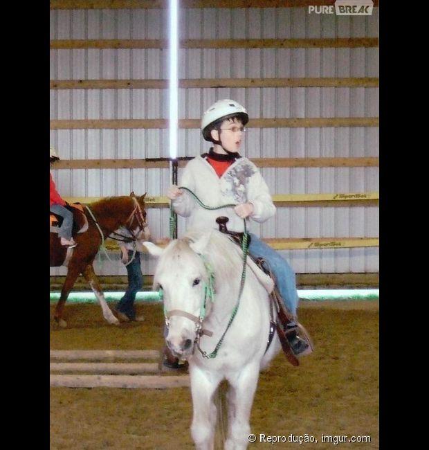 Garotinho em cima do cavalo com um sabre de luz